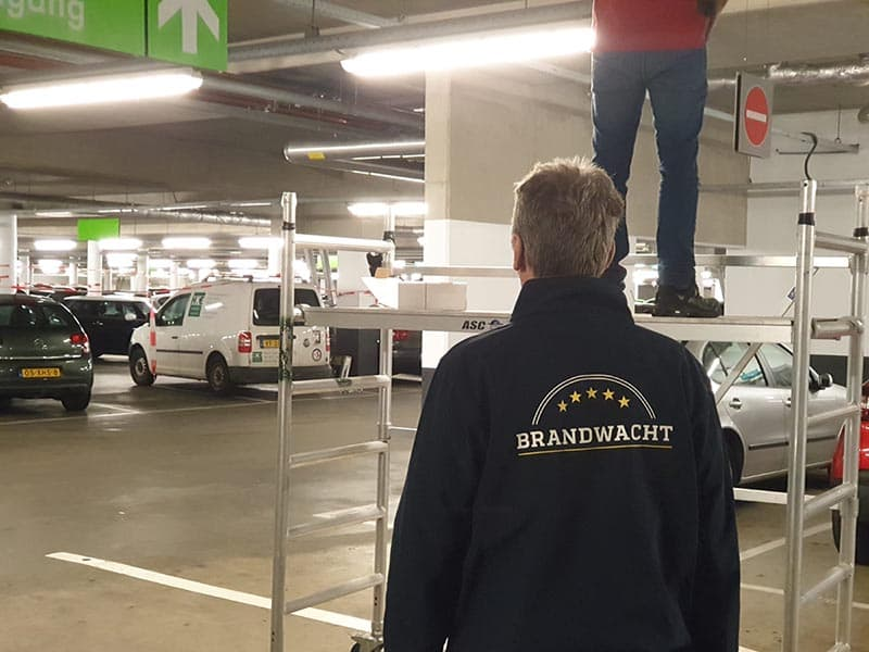 Voorkom brand bij werkzaamheden! Een brandwacht van Risk Safety is aanwezig tijdens het vervangen van de brandmeldcentrale (BMC) in een parkeergarage